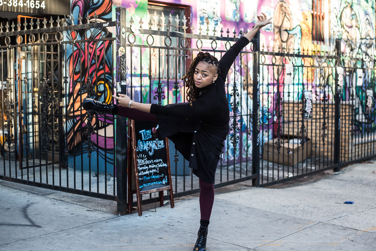 A woman tilts her body, extending one leg and both arms, in front of an iron fence and colorful graffiti