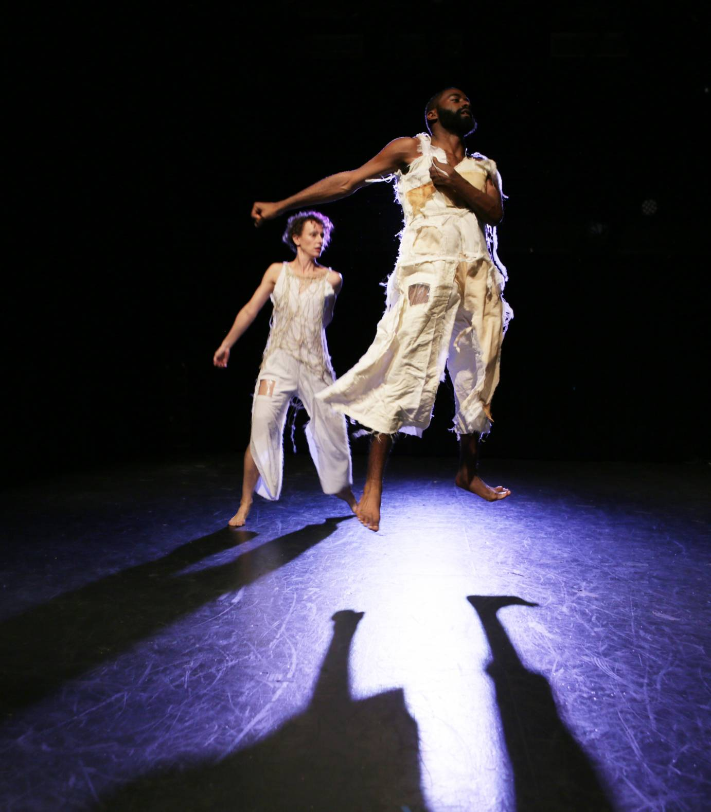 Two dancers jump with flexed feet