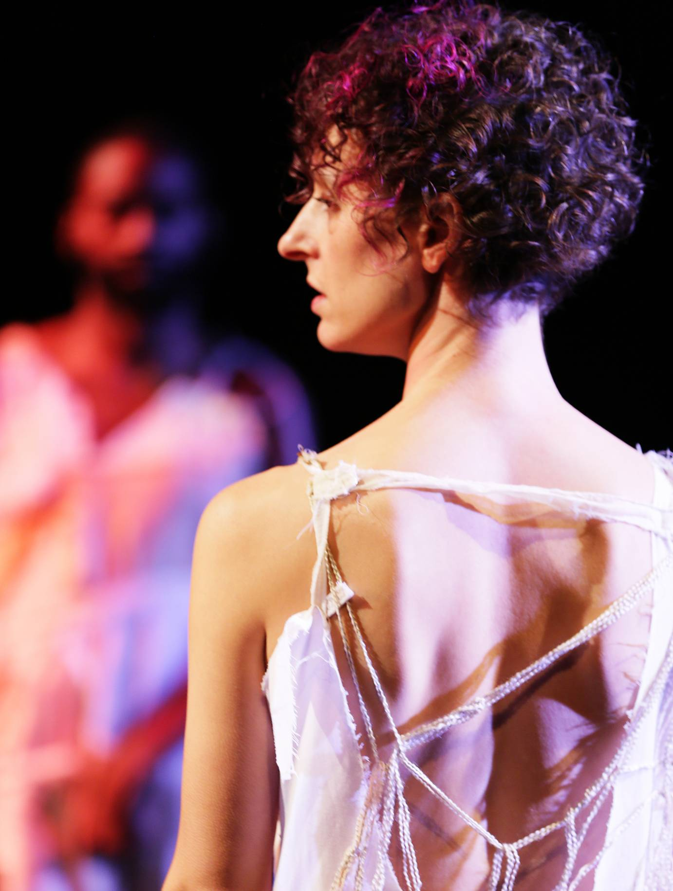 A profile of a female dancer with curly hair; another man is blurred in the background