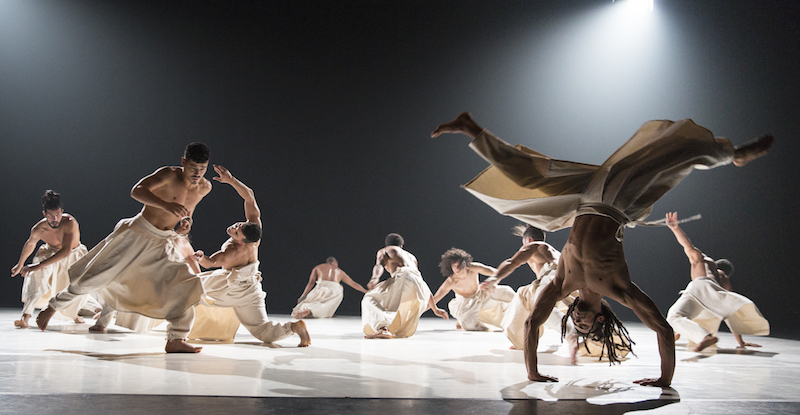 A group of bare-chested men in white flow-y pants spiral into the ground. One in the foreground is upside down in mid cartwheel.