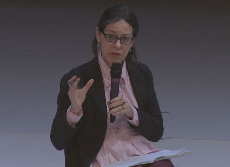 A close up of Panelist Annie B. Parson in a pink button up, dark blazer and glasses