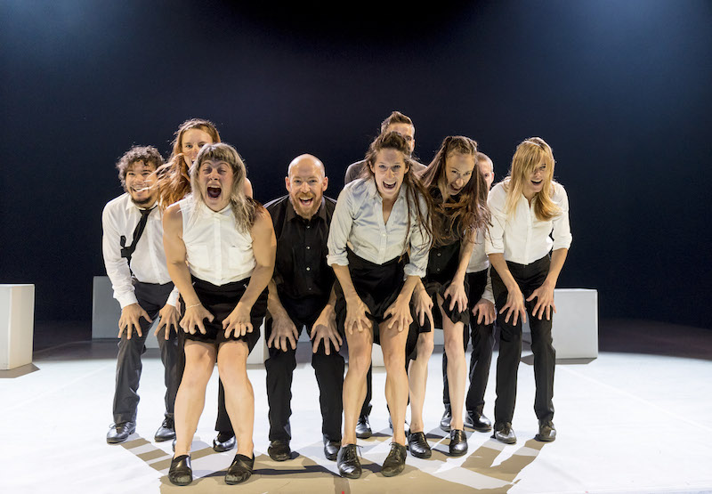 A group of dancers in business casual separates stand at the edge of the stage with open mouthed maniacal smiles