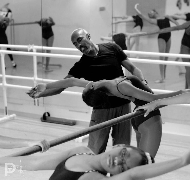 Bryant works with a young ballet dancer at the barre. He elongates her finger tips as she stretches back
