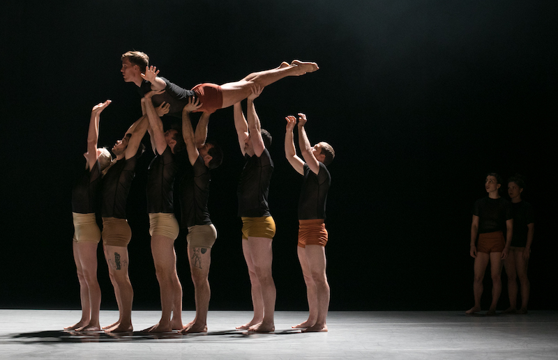 Dancers stand in a straight line holding another dancer above their heads.