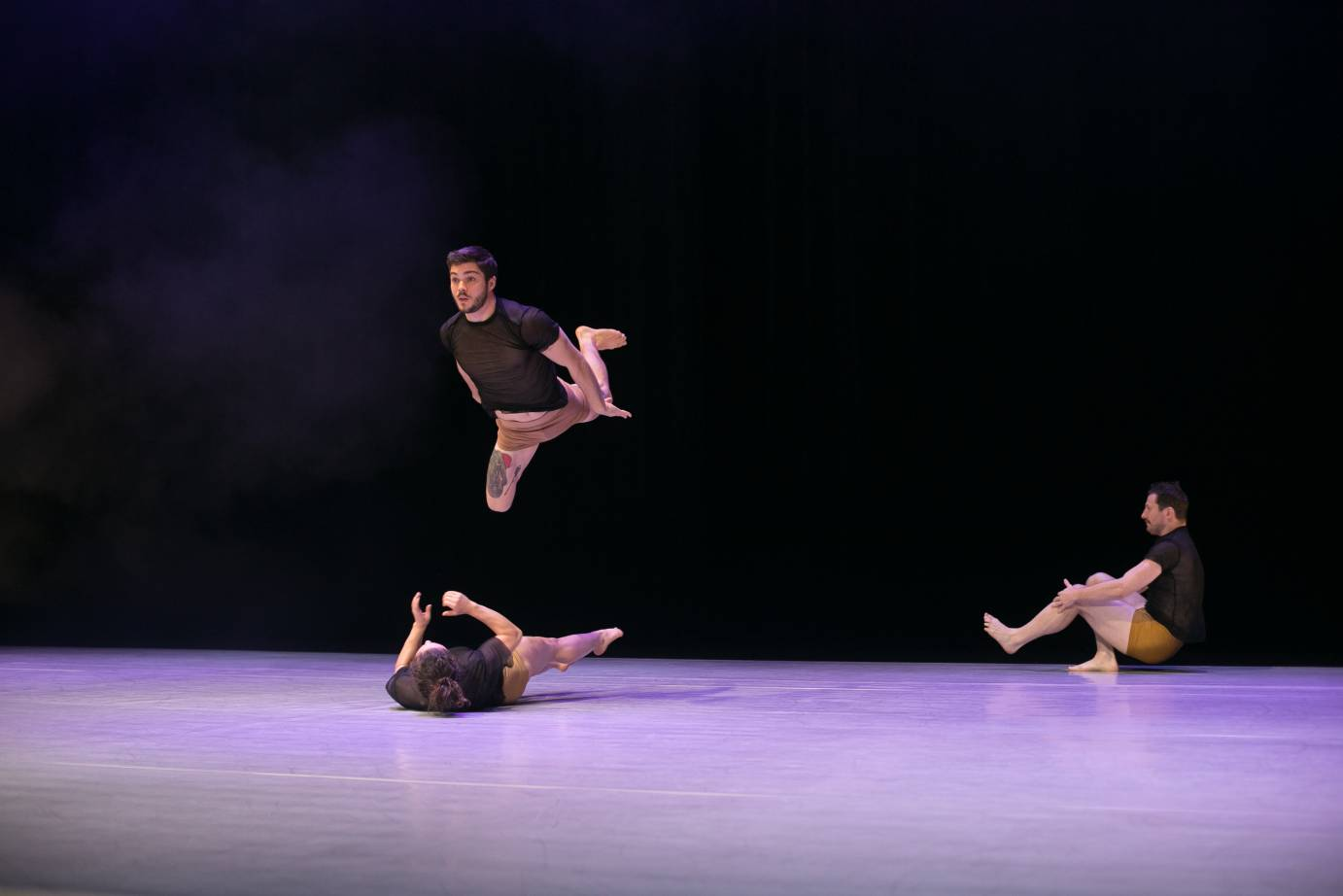 Two dancers roll on the floor while another jumps in the air parallel above one of them.