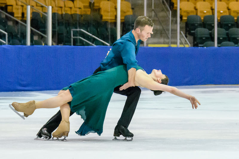 A woman lays back as her partner supports her behind her shoulders with his hands and his knee. They're low to the ice.