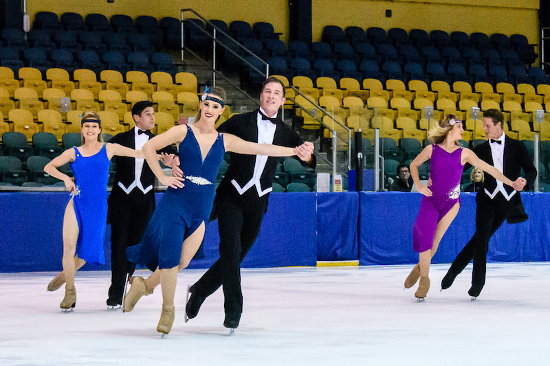 Three couples, the women in flapper-inspired blue dresses and the men in tuxes, skate hand in hand with their partners