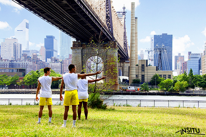 Three male dancers in yellow shorts and white t-shirts stand beneath the Brooklyn Bridge in Brooklyn Bridge Park with their arms outstretched.