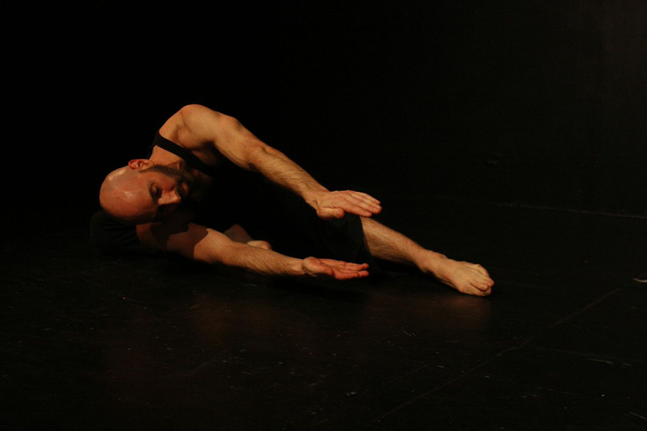 Dancer Daniel Gwirtzman lays on his right side, both of the hands extend towards the audience as if he is holding something between them