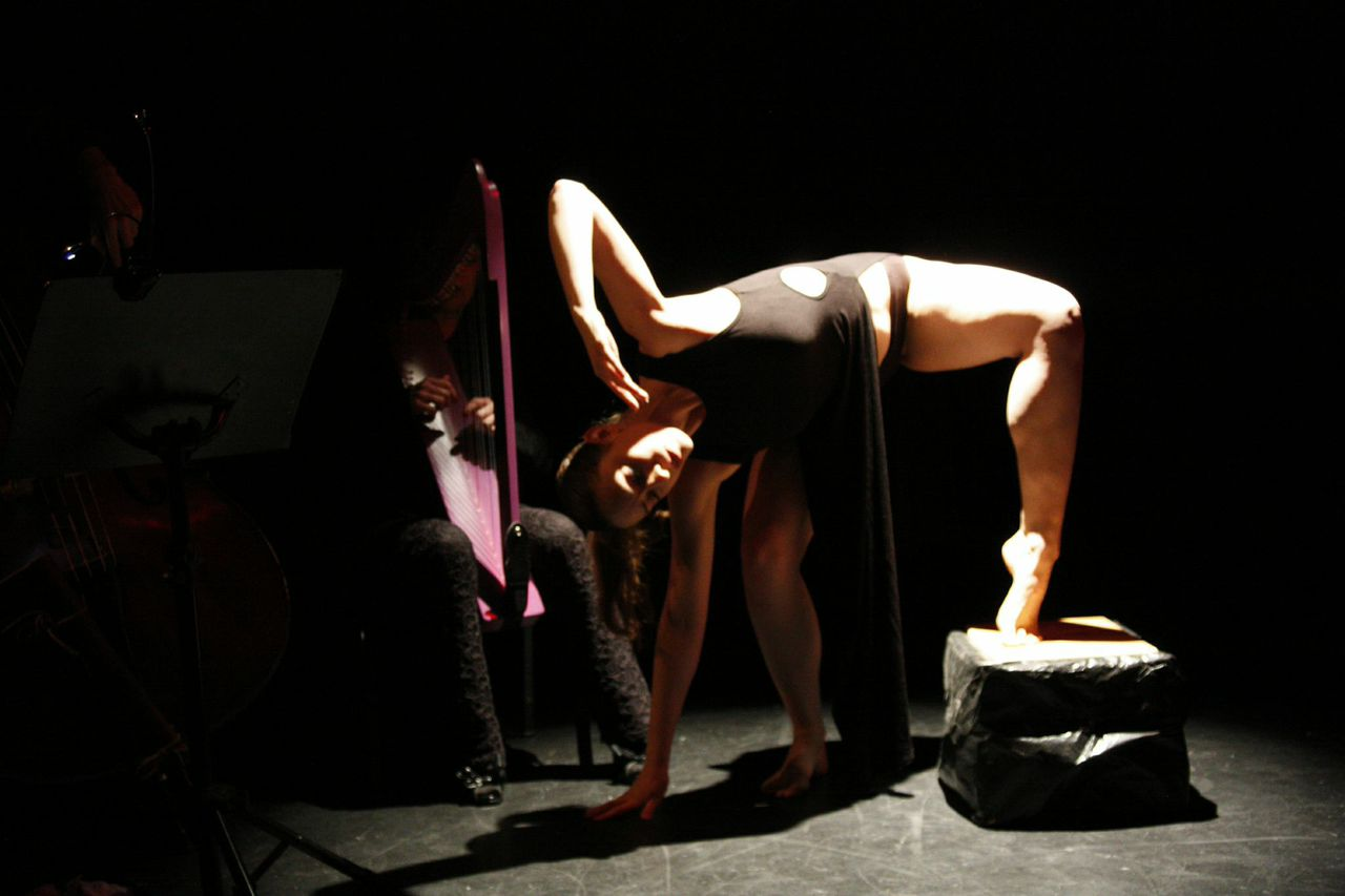 A woman balances one foot on the bread box while she leans over her right side. A harp player is in the background.