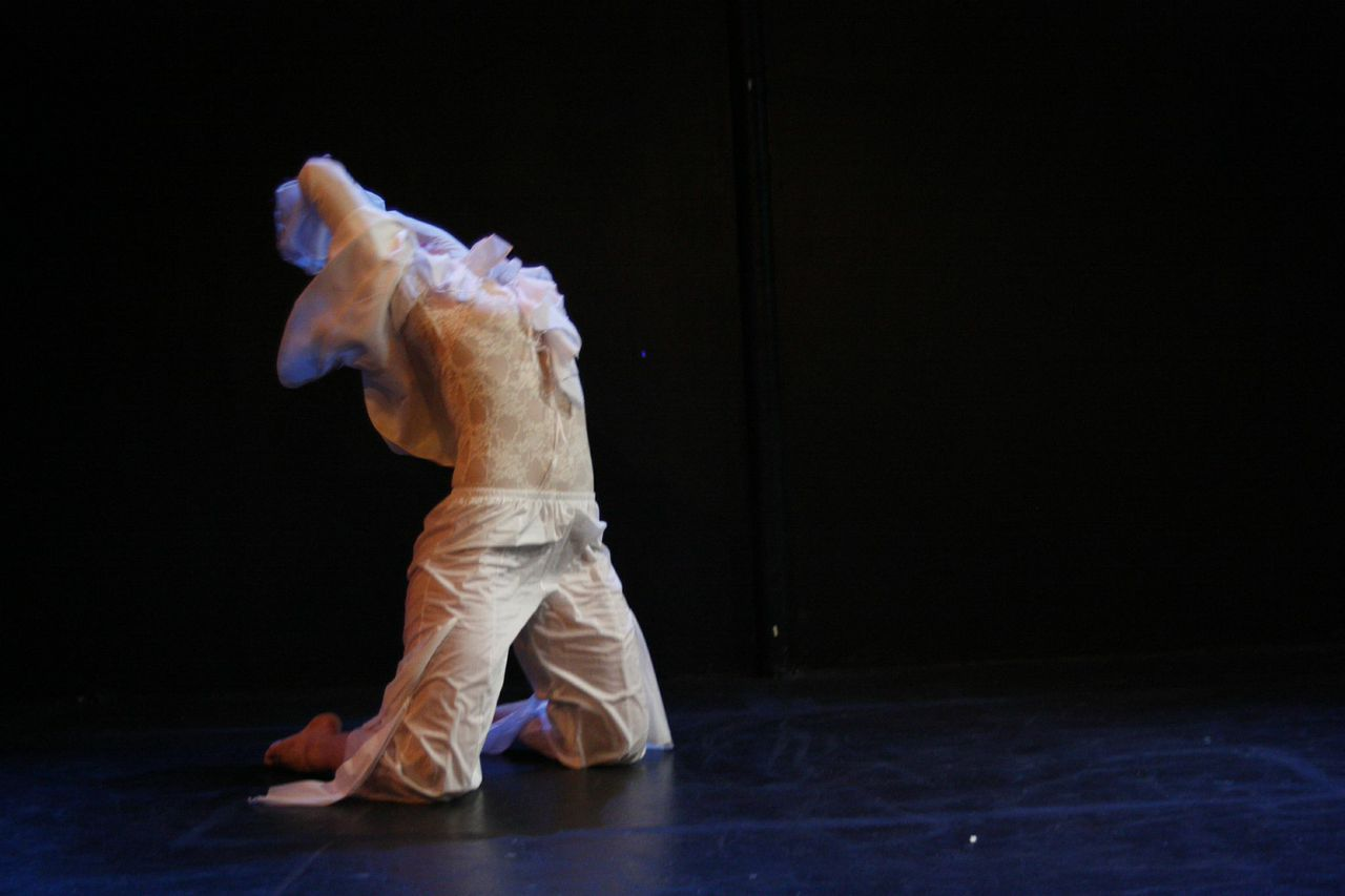 A female dancers executes a back end on her knees