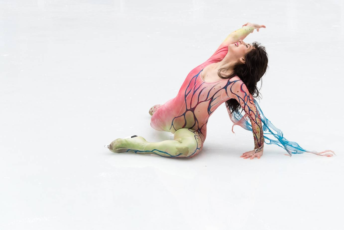 An ice dancer in a pastel colored unitard, lays on the ice and passionately raises her arm to the sky
