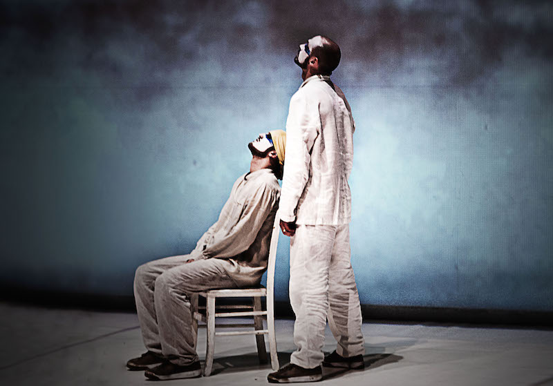 A man sits in a white chair while another hovers over him