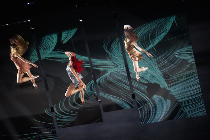 A view of the mirrored projection in Islands of Memories. We see the top of three women's heads. Their long hair flies as they spin on pointe.