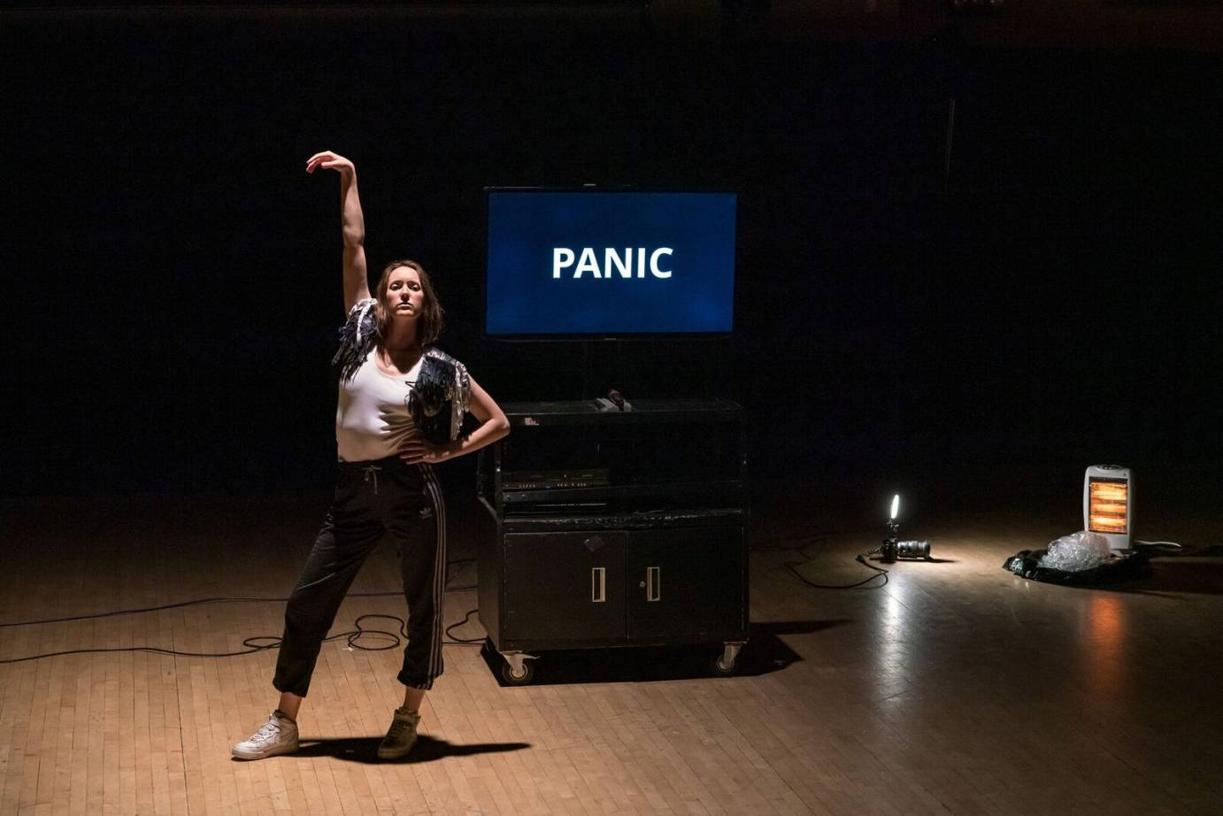 A woman strikes a disco pose in front of a video that says PANIC