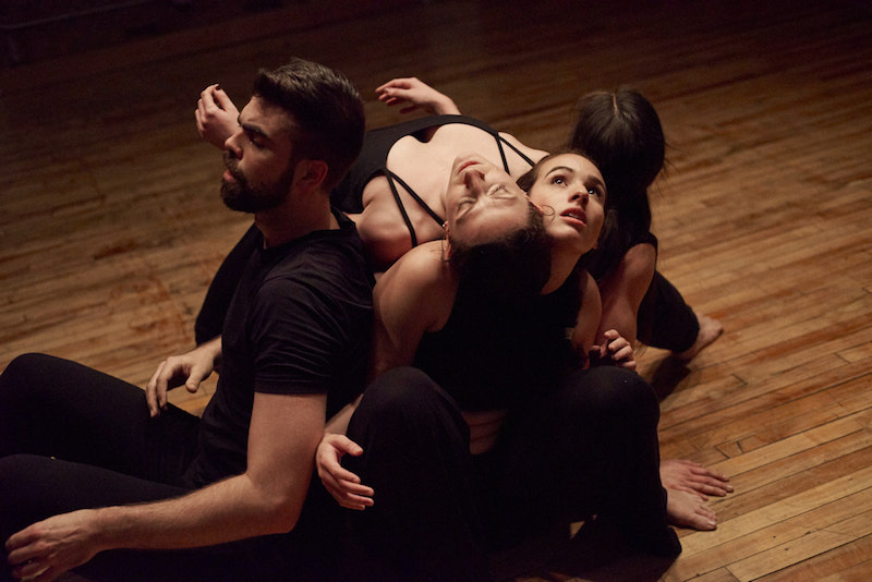 Four dancers sit in a tight-knit clump. One dancer lays her back and head on her fellow performers. Another looks up to the ceiling.