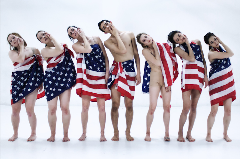 A group of dancers stand in a line with American Flags wrapped around their bodies. They each rest their right hand on their left cheek.