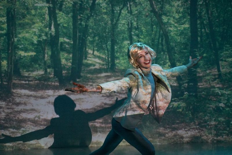 A woman in a blonde wig smiles and opens her arms in front of a forest projection.