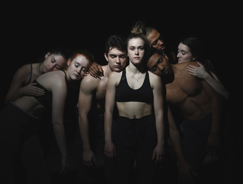 A group of dancers huddle in a group and lean on one another. They each close their eyes with the exception of one woman who stares directly at the camera.