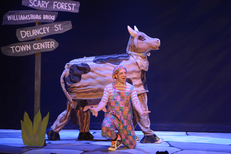 Actor Matt Roper in plaid overalls kneels in front of a cow puppet. A sign that displays