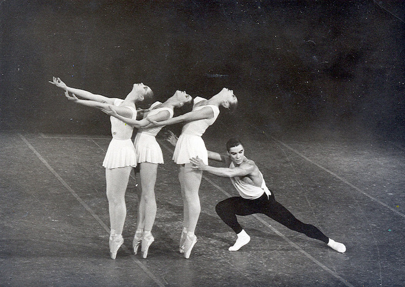 Three female ballet dancers stand on pointe with the heads back while Jacques extends into a lunge behind them