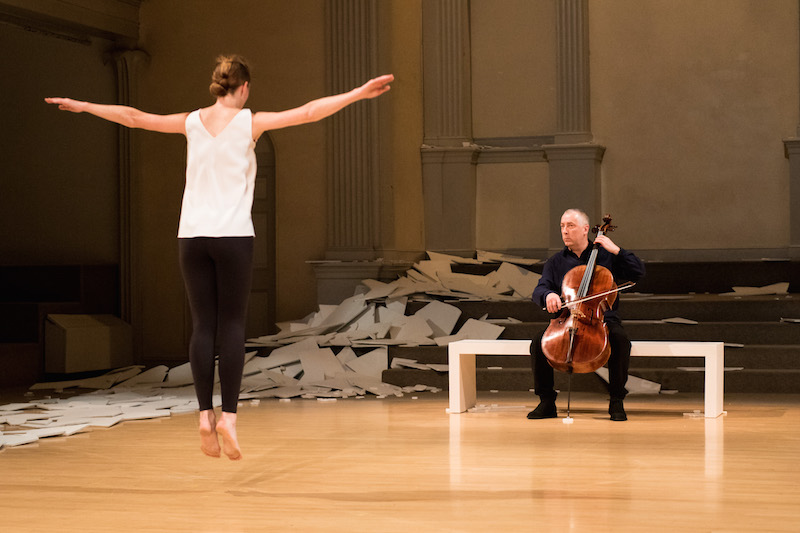 Butler leaps in the air with her back to the audience and her arms outstreched, Martin watches her as he plays the cello on the bench