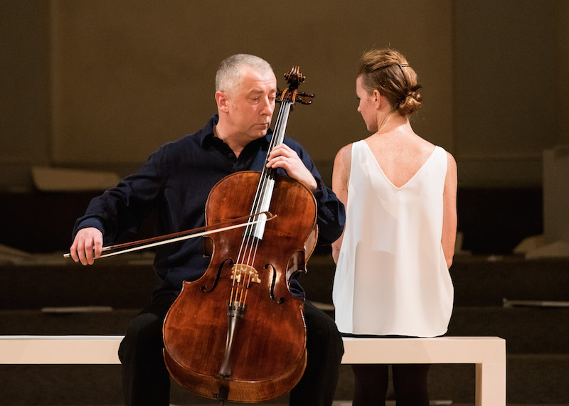 Jean Butler and Neil Martin sit on a white bench as Martin plays the cello