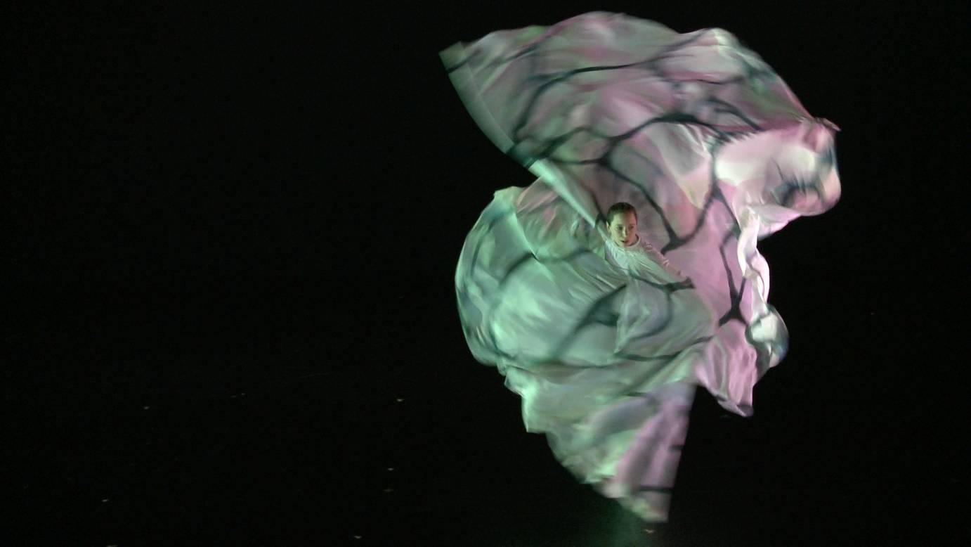 A woman in a flowy gauzy dress spins. The layers of fabric cascade around her.