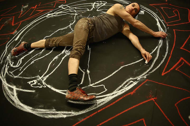 John Kelly lays on the ground and draws around himself with red and white chalk. Various lines and designs flank him.