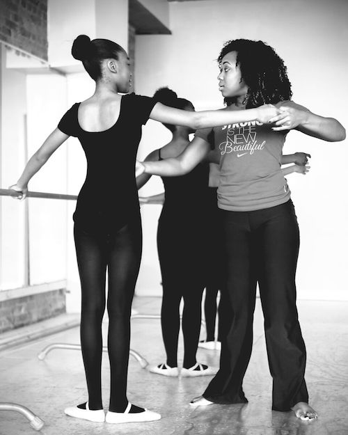 Karisma Jay helps a student at the ballet barre. The students wear black leotards and tights and stand in first position. Jay helps a student lengthen her arms.