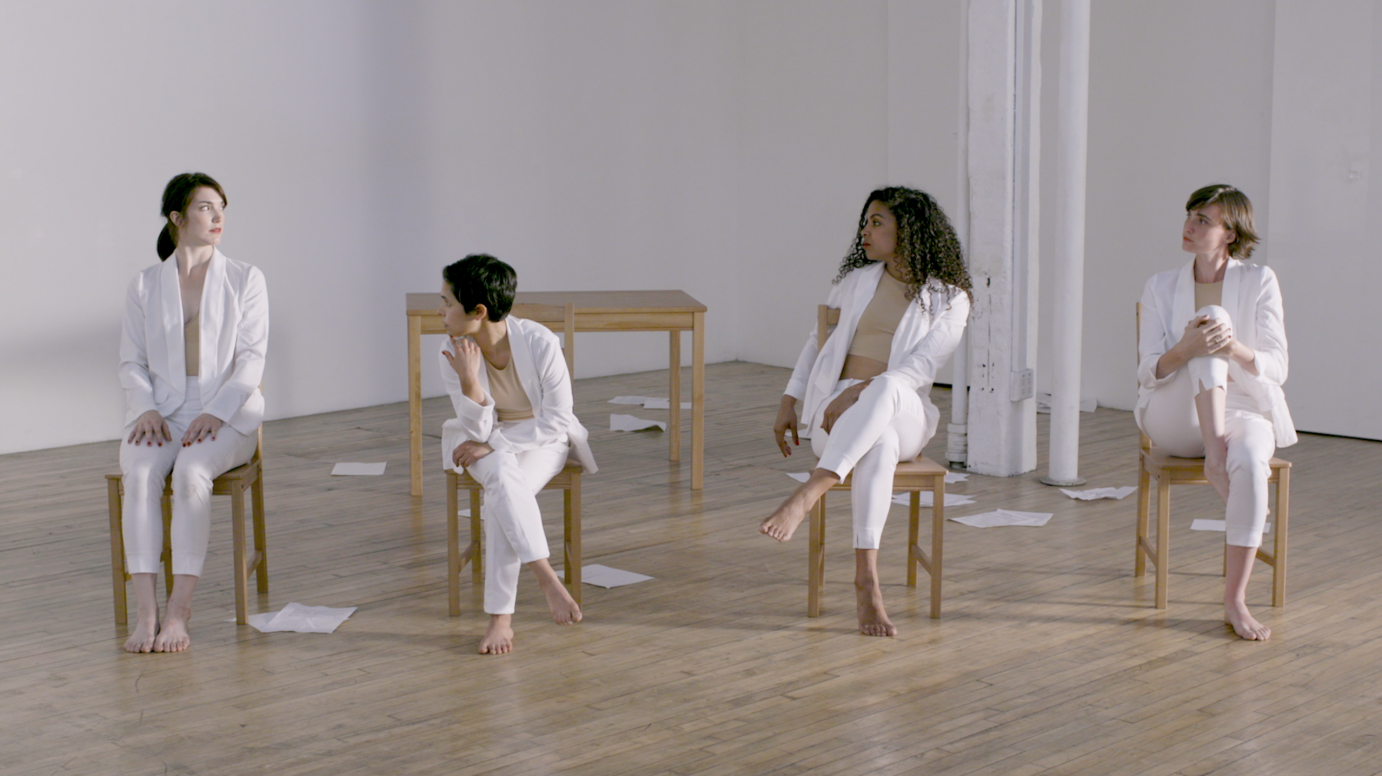 Four women in white suits sit on wood chairs and look at one another. Paper is strewn about the floor.