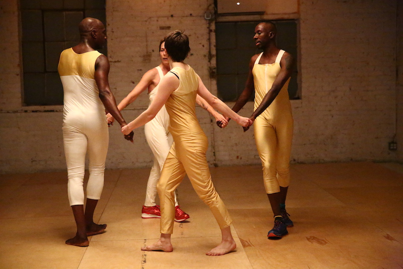 Four dancers in gold and white unitards stand in a circle and hold hands