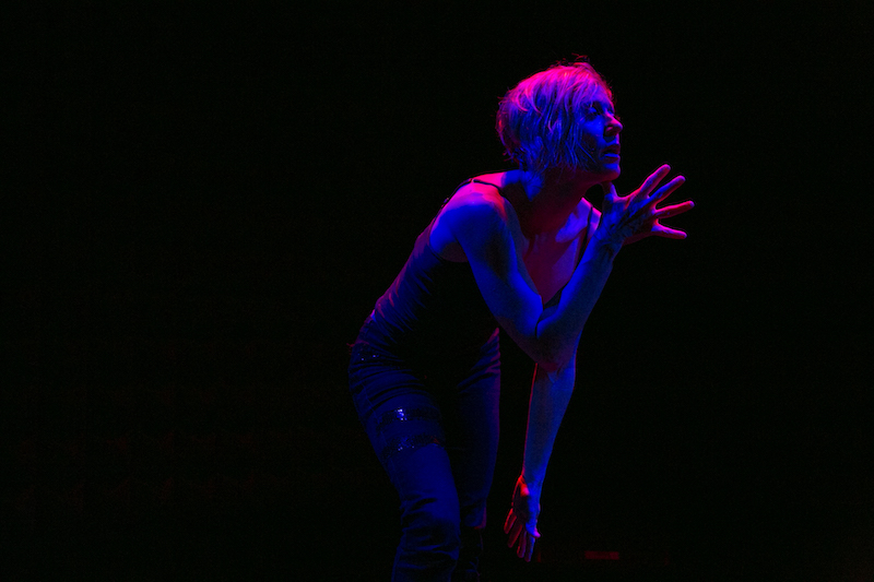 Nicole Wolcott in rose-colored light gestures with her right hand, her fingers splayed, in front of her