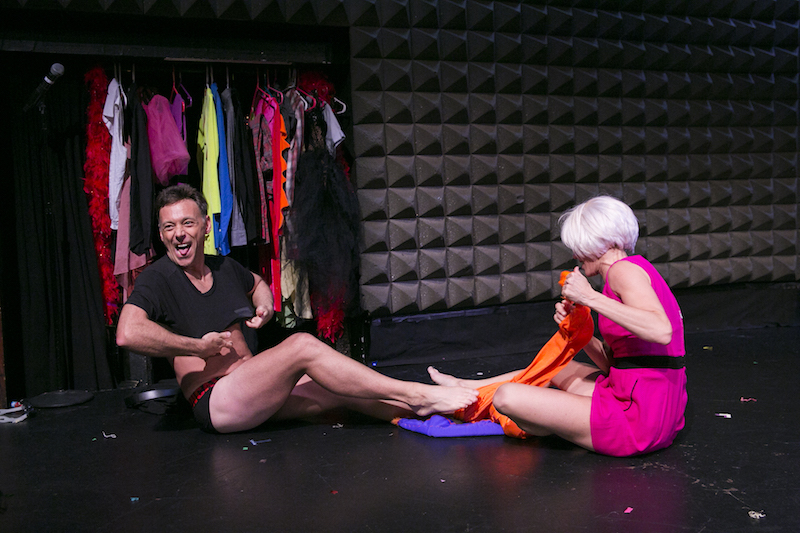 Larry Keigwin and Nicole Wolcott in a blond wig sit on the floor and change costumes. A garment rack filled with colorful outfits is in the background.