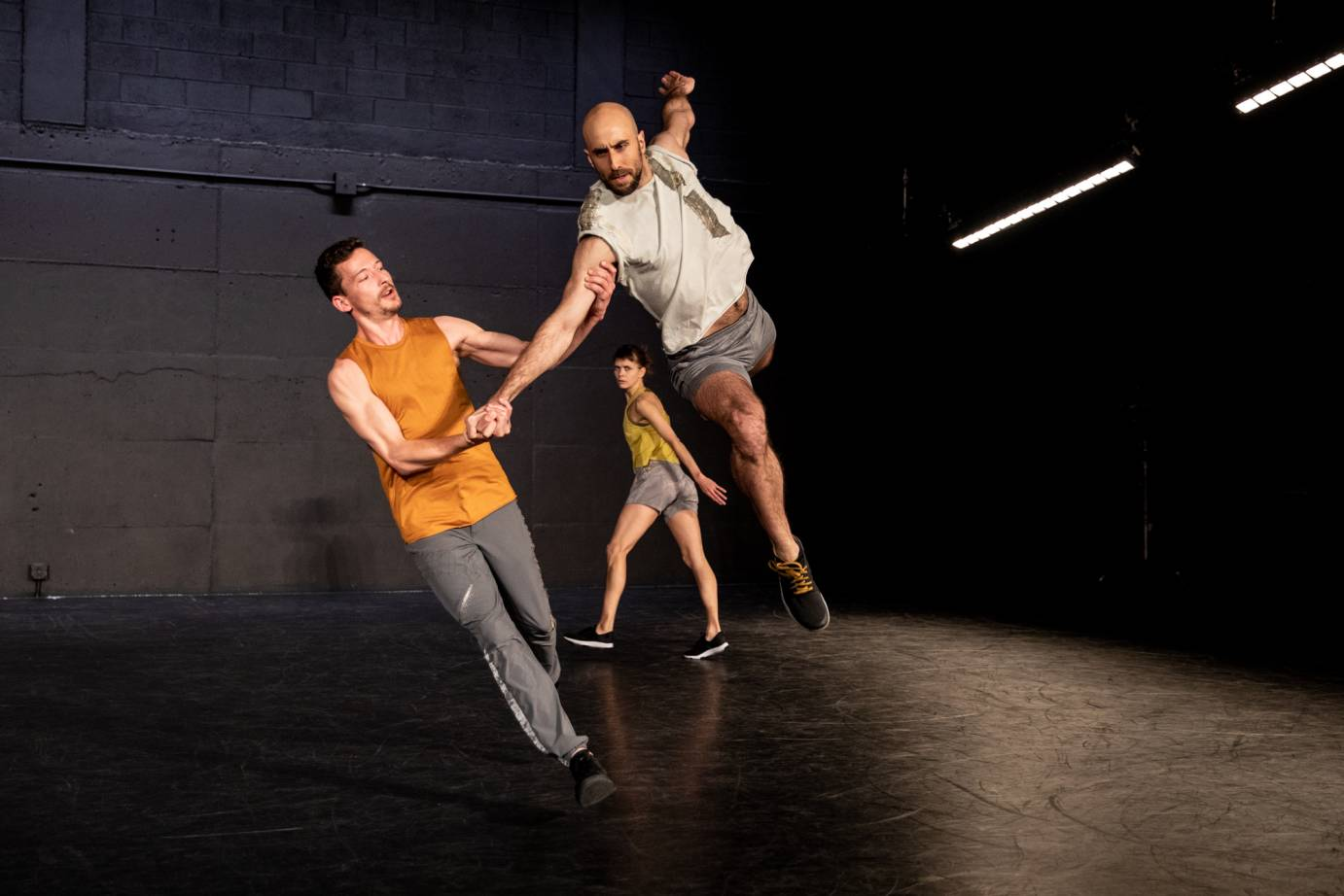 One man partners another in a stage leap as a woman looks on in the background