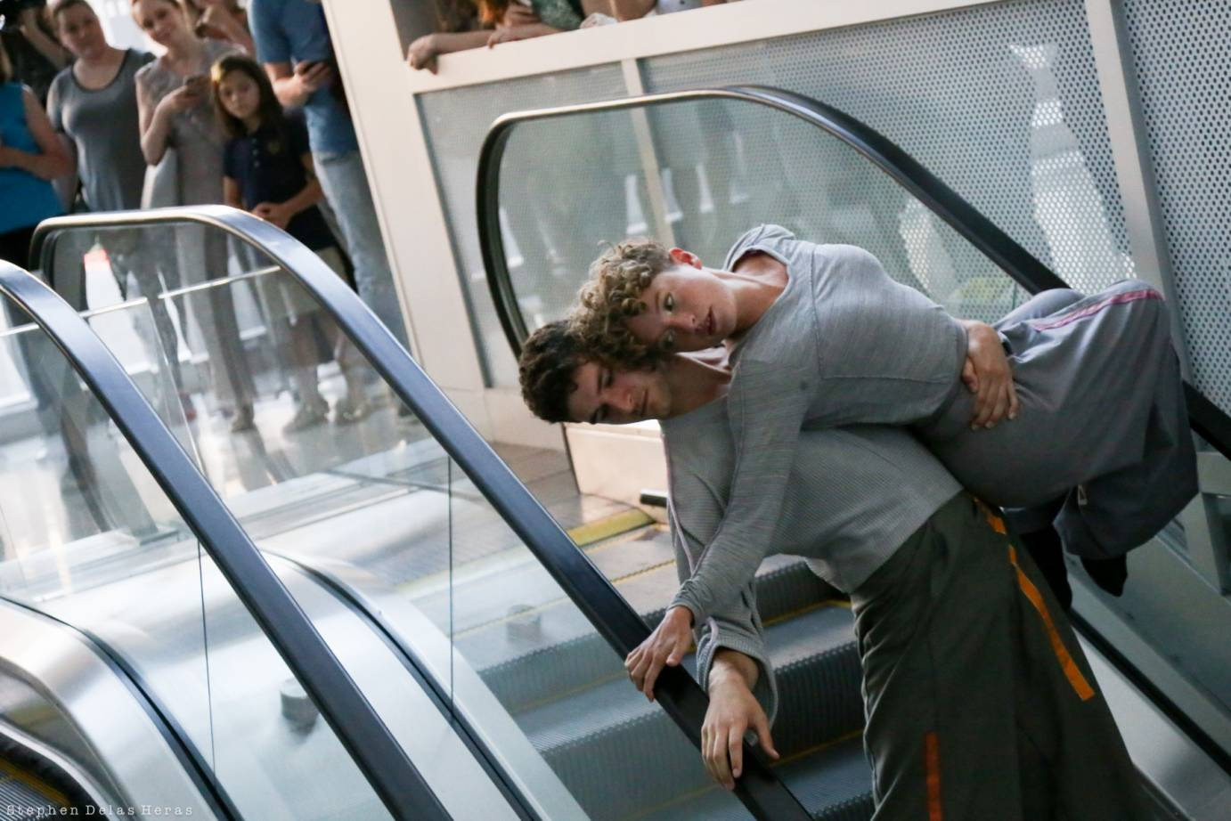 Two dancers in grey dance on a escalator. One performer picks up the other.