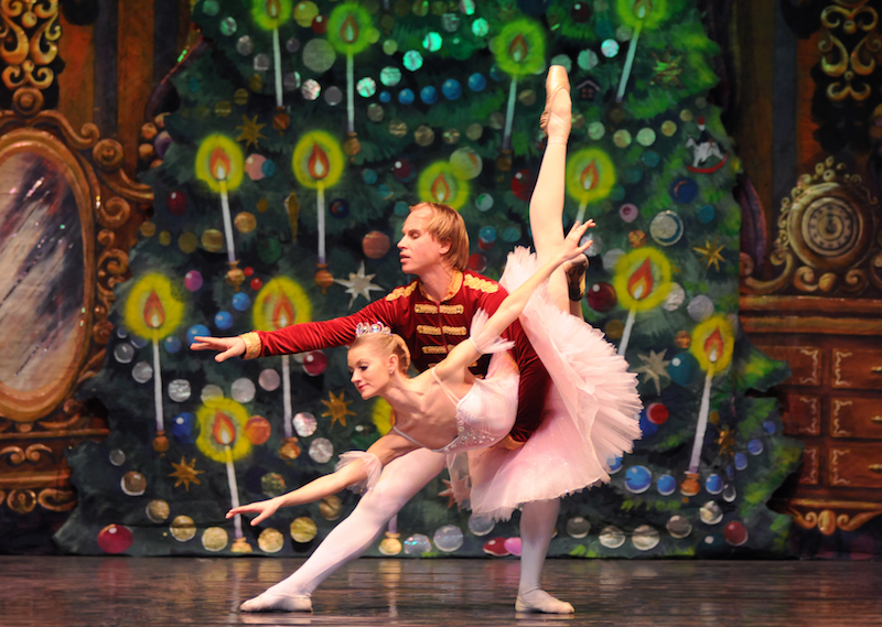 Russian ballet dancers pose in front of the Land of Sweets Nutcracker backdrop. The male in the role of prince holds his female partner in the dipped