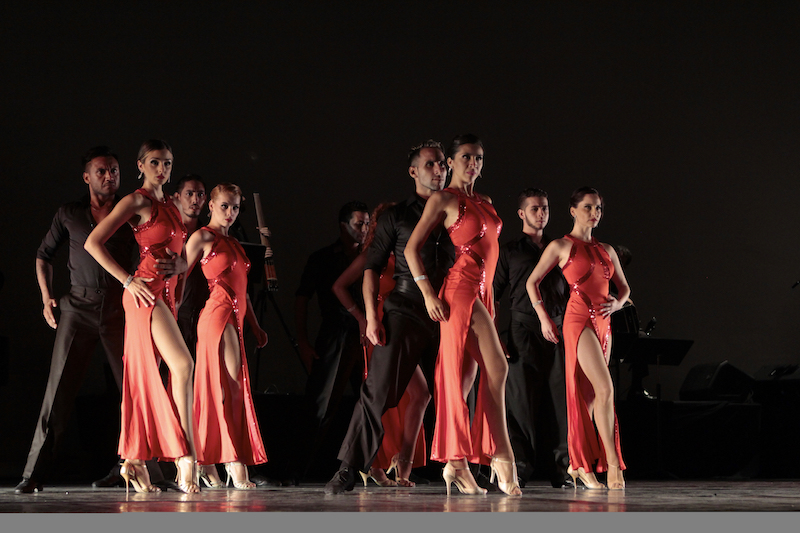 Tango dancers stand with their partners. The men wear all black and the women wear orange dresses with slits up the right thigh.