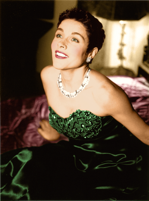 A woman in an emerald strapless dress and sparkly necklace and earrings.