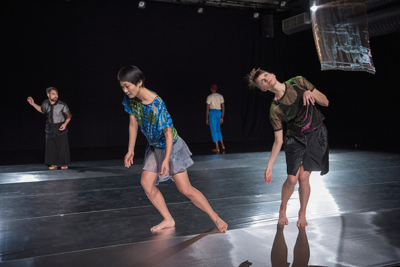Two women in silk tops and skirts are in the background. Two others dancers stand in back. One wears a black filmy blouse and black skirt while the other faces the back curtain in blue pants and white tee.