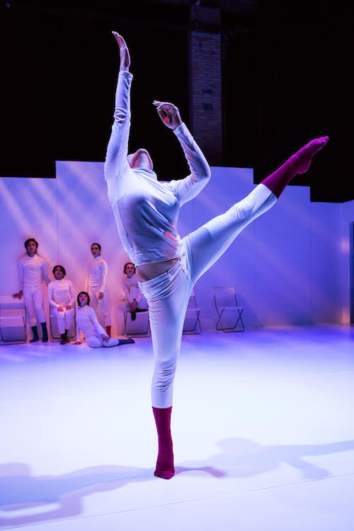 Dancers huddle together against a white wall while they look over to a dancer who extends their left leg high into the air