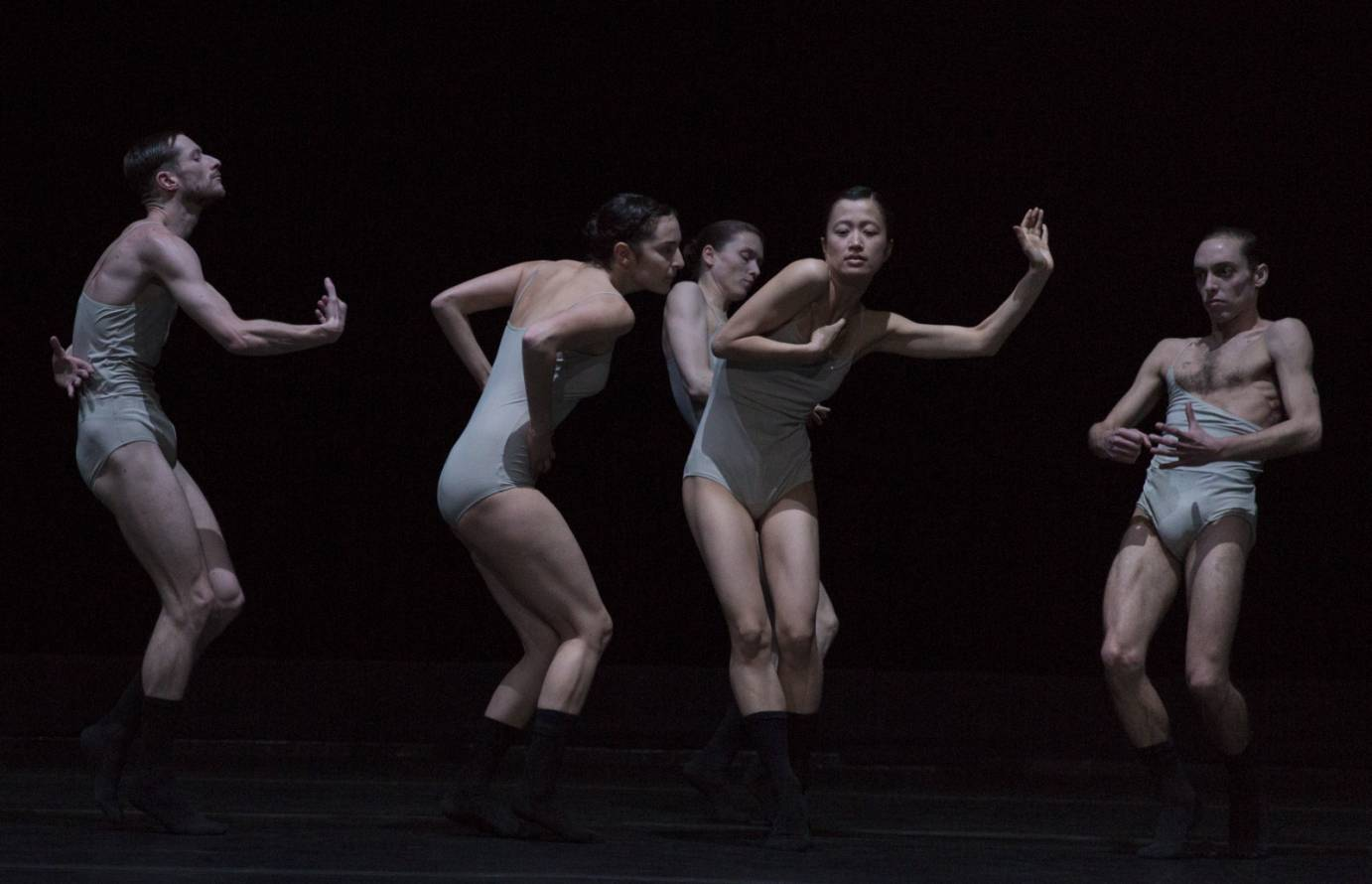 One dancer is surrounded by other dancers writhing