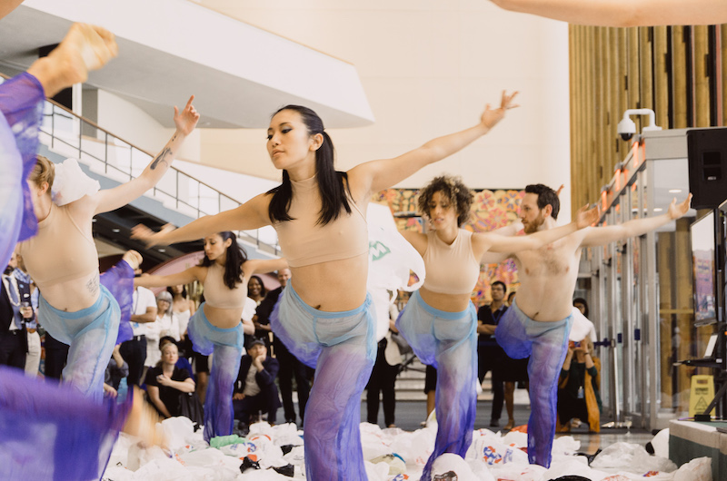 Dancers in purple tie dye pants and nude crop tops strike a pose with one leg bent behind them in a white lobby. Plastic bags are strewn about their feet. A crowd watches in the background.