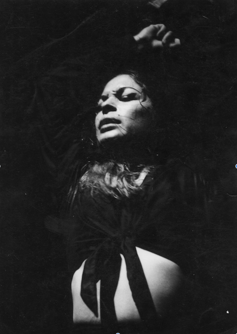 La Chana dances passionately with her arms above her head. The photo is in black and white and taken when La Chana was a young woman.