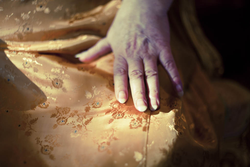 A close up of hands resting on the lap of a woman in a gold satin dress.