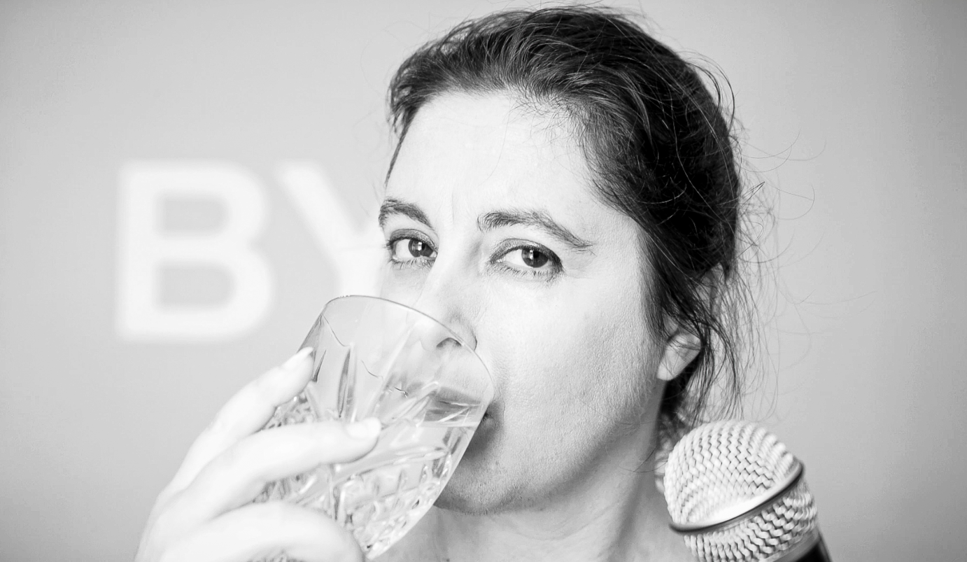 In a black and white picture, Anabella Lenzu drinks from a glass of water while holding a microphone