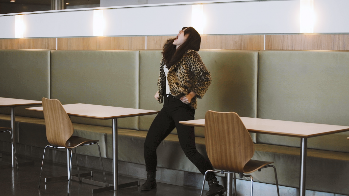 Ida Haugen screams in between cafe tables while wearing a leopard print jacket.