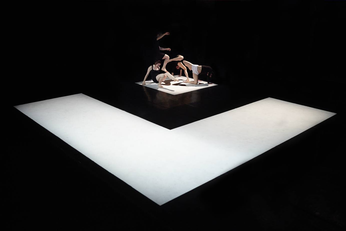 On a floor of a big white square holding a small black one, performers crouch with a leg or arm extended
