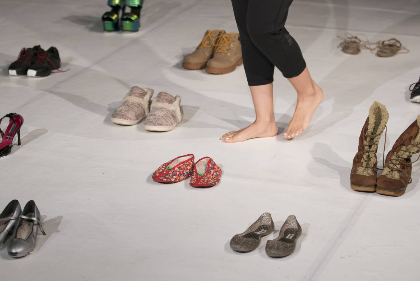 Woman's legs among a grid of paired shoes
