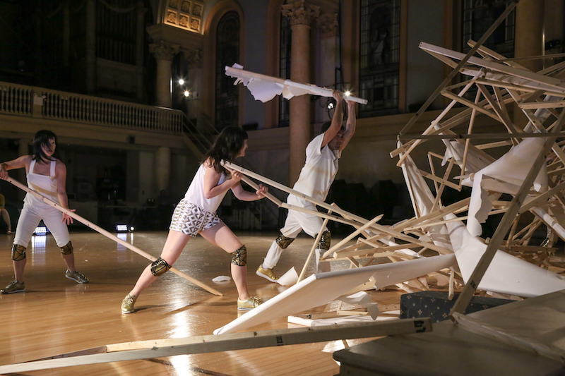 Dancers in white and gold costumes and knee pads destroy the installations